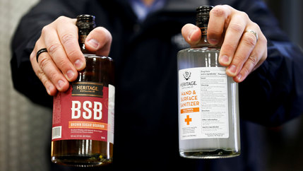 A close up of hands holding a bourbon bottle and a bottle of hand and surface sanitizer