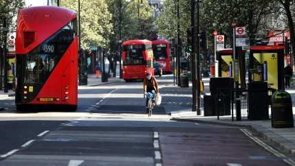 Three red, double-decker buses are shown driving on a nearly empty street that also includes a lone bicyclist.