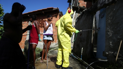 A worker is shown in a full protective yellow suit and is spraying a cleaner with several other people standing by watching.