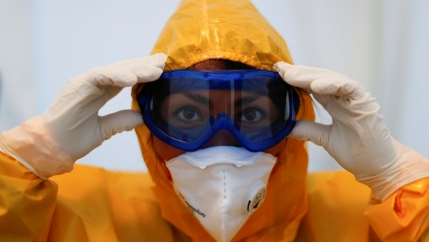 A health care worker is shown in a closeup photographer wearing protective goggles, face mask and a medical gown.
