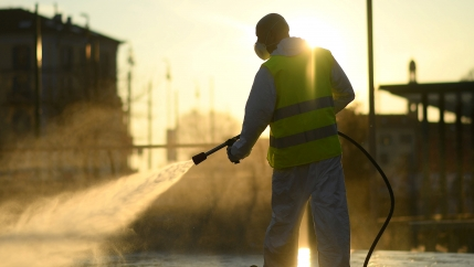 A man sprays a street with sun streaming in as he wears protective gear.