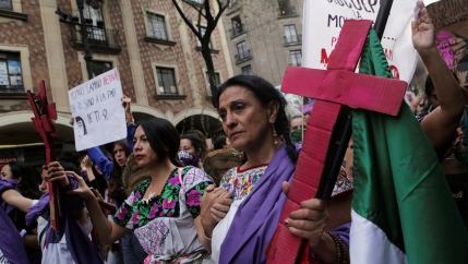 A woman holds a pink cross during a protest to mark International Women's Day at Zocalo square in Mexico City, Mexico, March 8, 2020.