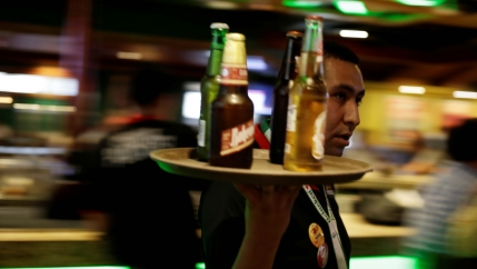 A waiter carries a round tray with bottles of Mexican beer at a bar in Ciudad Juarez, Mexico, on June 20, 2017.