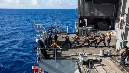 US Navy sailors raise a larne target from the fantail of the aircraft carrier USS Theodore Roosevelt in the Philippine Sea on March 21, 2020.