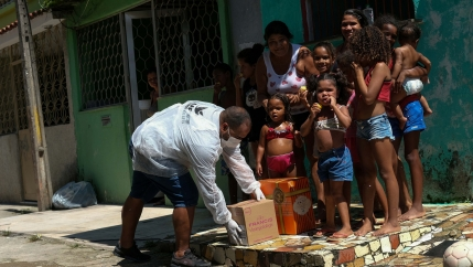 A volunteer delivers donated aid to poor families in Rio de Janeiro's slums through Single Centre of Slums (CUFA) during the coronavirus disease (COVID-19) outbreak, in Vila Kennedy slum in Rio de Janeiro, Brazil, on April 2, 2020.