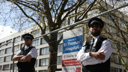 Two police officers are shown with their arms folded and standing in front of a fence with St Thomas' Hospital  in the background.