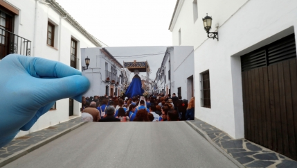 A photographer wearing a protective blue glove and is holding a picture of the very street they are standing in — presently empty and in the photo filled with people.