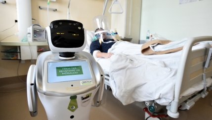 A picture of a robot in a hospital room and a patient laying on the bed sick.