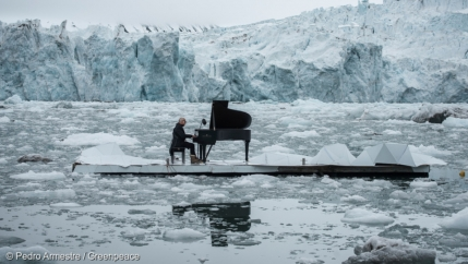 A man plays the grand piano on a floating platform in front of a glacier.