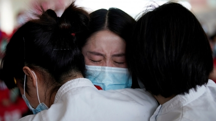 A close-up photograph of three women are shown hugging and wearing protective face masks.
