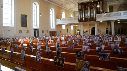 A church sanctuary is shown with empty rows of pews and the photos of people's faces taped to the back rest.