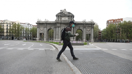 A man wearing a protective face mask and gloves walks past the empty landmark Alcala Gate