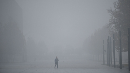 A man in the middle of a smog-filled street