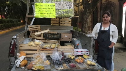 A woman stands by a display of fruit