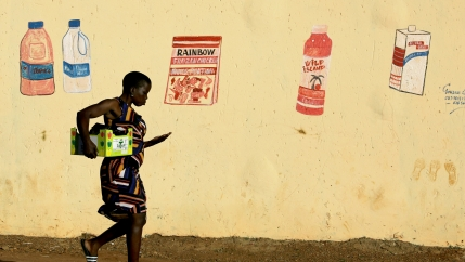 A woman walks home in front of a wall with supermarket mural of grocery items
