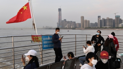 People in face masks ride on a ferry with a Chinese flag