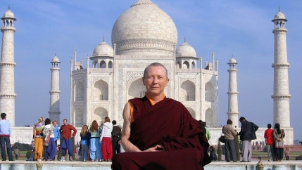 A Buddhist nun sits in front of the Taj Mahal