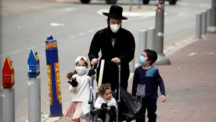An ultra-Orthodox Jewish family wearing masks