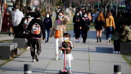 A girl wearing a protective face mask to prevent contracting the coronavirus disease (COVID-19) rides a toy kick scooter at a park in Seoul, South Korea, April 3, 2020.