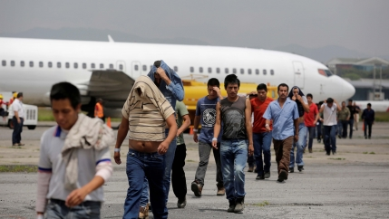 Deportees cross the tarmac after arriving on an immigration flight from the US at La Aurora international airport in Guatemala City, Guatemala, on Sept. 2, 2016.