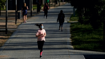 A woman wearing a protective face mask runs in Madrid Rio park, during the hours allowed for individual exercise.