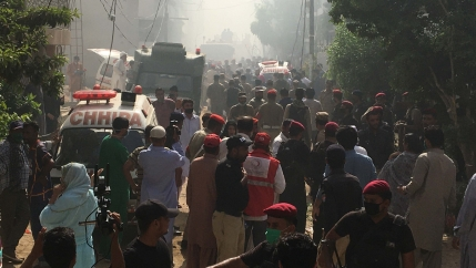 Ambulances and fire brigade vehicles gather at the site of a passenger plane crash in a residential area near an airport in Karachi, Pakistan, on May 22, 2020.