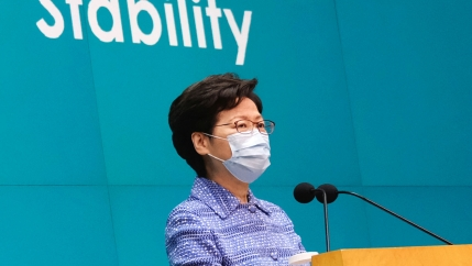Hong Kong Chief Executive Carrie Lam is shown standing at a wooden podium with two small microphones and wearing a protective face mask.