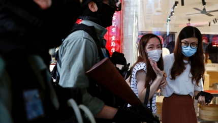 Two women are shown wearing protective face masks as several police officers walk past carrying weapons and wearing protective riot gear.
