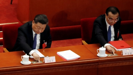 Chinese President Xi Jinping and Premier Li Keqiang are shown sitting in red chairs and pressing buttons in front of them to cast their vote.