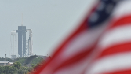 A US flag flutters in the breeze. In the background, a rocket launchpad