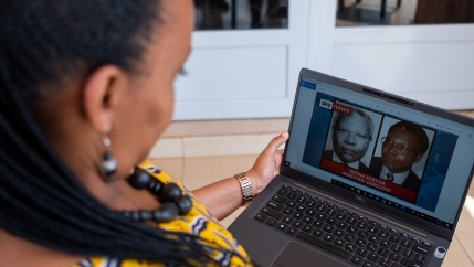 A woman wearing yellow blouse looks at images of men on a computer screen