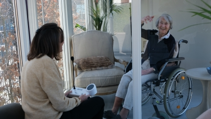 A younger woman looks at an older woman behind glass at The Glass Garden House at the Claris nursing home.