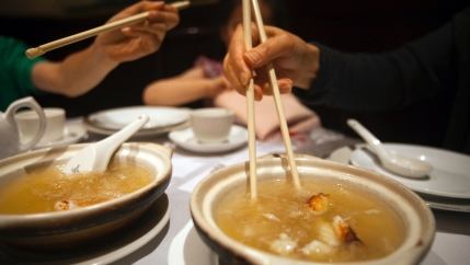 Two people eat with chopsticks at a restaurant