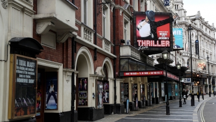 West End theaters stand on a sparsely populated street in London, March 13, 2020.