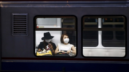 Women wearing masks to prevent contracting Middle East Respiratory Syndrome (MERS) ride a subway train in Seoul, South Korea, on June 12, 2015.