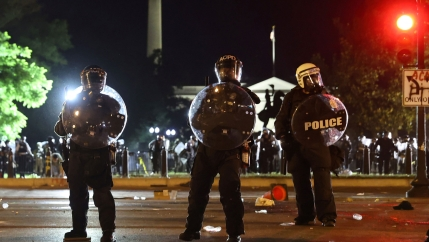 Several police officers are shown carrying shields and wearing riot gear with the White House in the background.