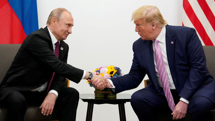 Russia's President Vladimir Putin and US President Donald Trump are shown sitting in arm chairs and leaning toward each other shaking hands.