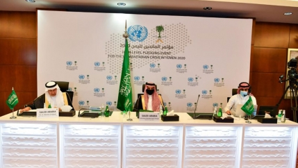 Three men are shown wearing traditional Saudi headdress and garments while seated at a long white table.