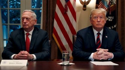 US President Donald Trump is shown sitting at a wooden table next to then Defense Secretary James Mattis with the US flag behind them.