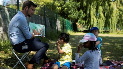 Three children sit on the ground as a male teacher reads a picture book