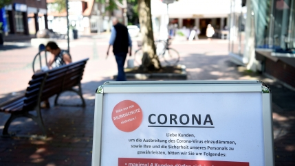 A quiet street is shown with a white sign with warnings about the coroanvirus printed on it in the nearground.