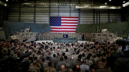 A crowd of US service members stand in front of Trump, with a large US flag in the background