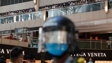 A helmeted head is blurry in the foreground, behind it, a line of protesters on a balcony