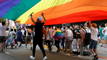A group walks under a large rainbow flag.