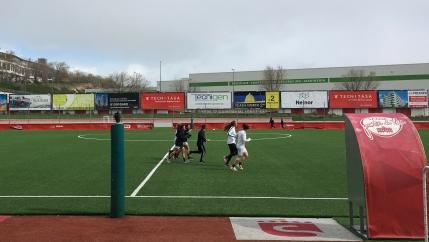 Women run on a soccer field