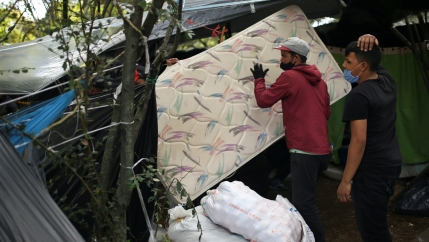 A man wearing a face mask carries a mattress at a makeshift camp