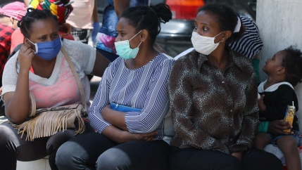 Four Ethiopian women wearing blue face masks sit outside with a young child.