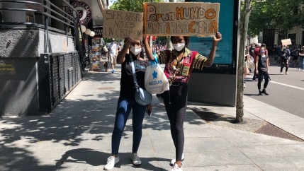 Two protesters hold signs with anti-racist messages