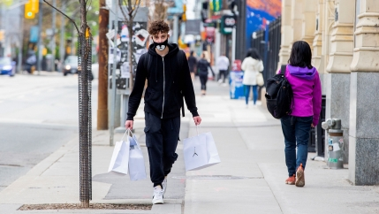 Nick Abrantes walks after purchased three pairs of shoes during a phased reopening from the coronavirus disease (COVID-19) restrictions in Toronto, Ontario, Canada May 19, 2020. REUTERS/Carlos Osorio/File Photo