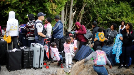 A Royal Canadian Mounted Police (RCMP) officer announces to a group of asylum-seekers that they will be crossing illegally into Canada as they wait in line to to enter at the US-Canada border in Champlain, New York, August 7, 2017.